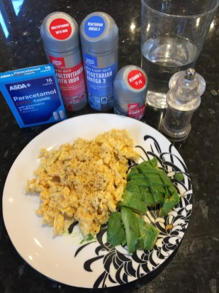 Scrambled eggs with avocado and a variety of vitamin pills