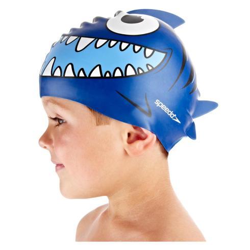 A small boy wearing a blue fish swimming hat.