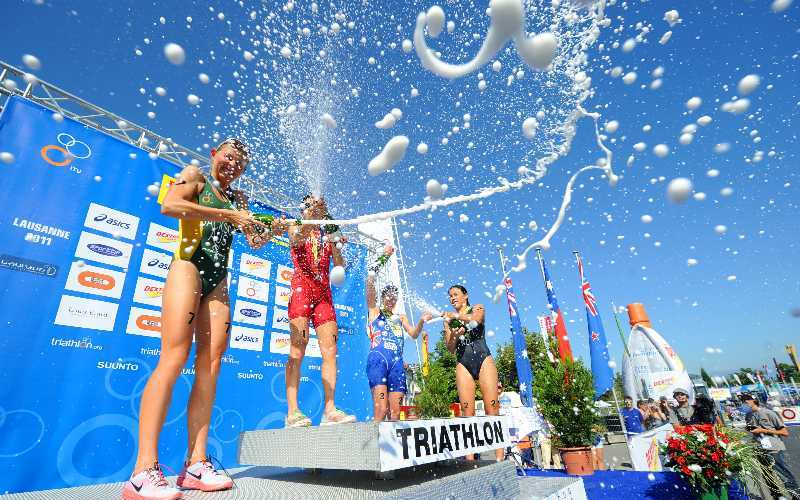 Women spraying each other with champagne on a triathlon podium