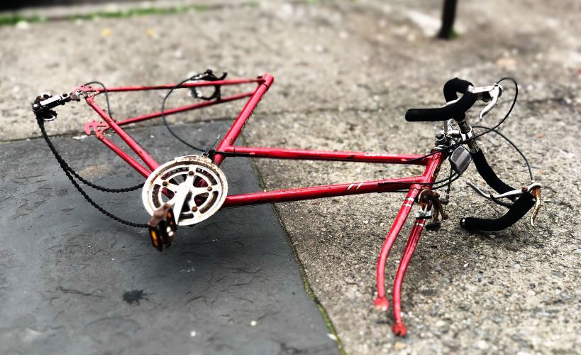 A vandalised bike with no wheels or saddle