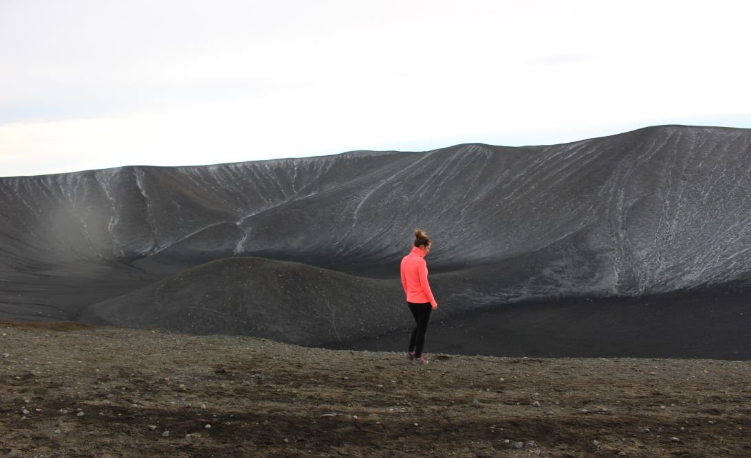 Woman in a neon jacket against a backdrop of a volcanic landscape