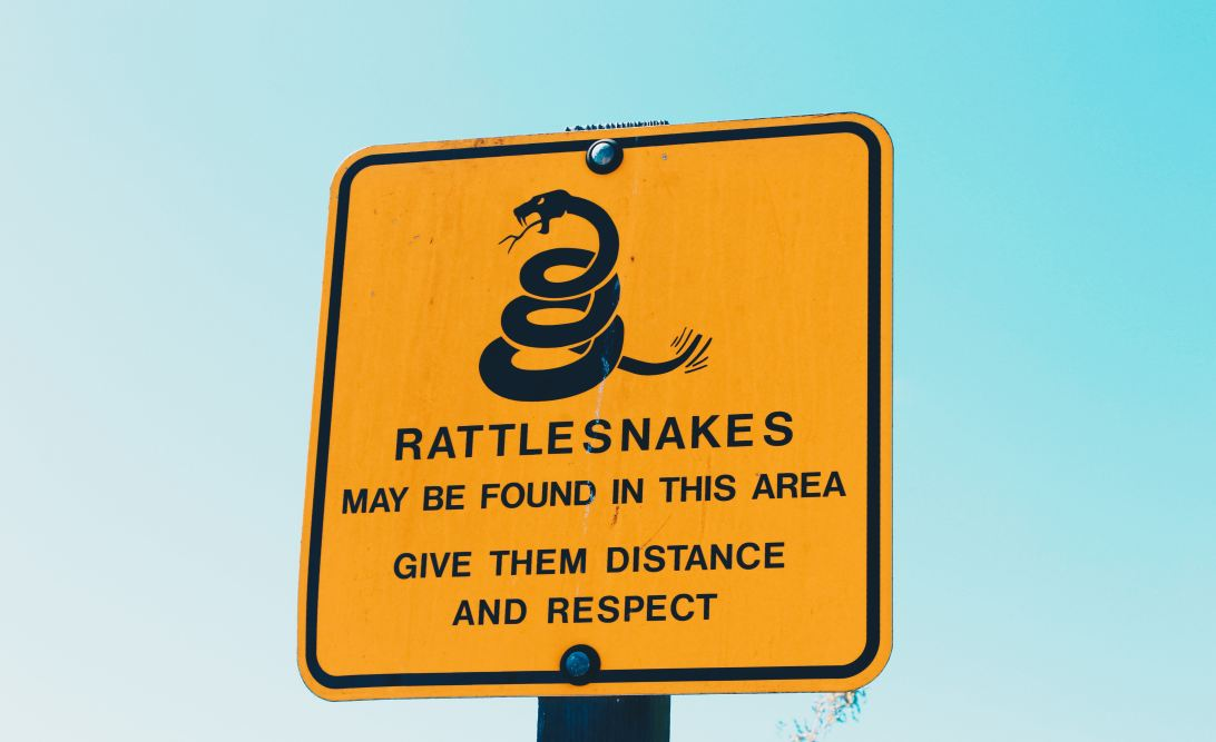 Warning sign saying 'Rattlesnalkes may be found in this area. Give them distance and respect.'