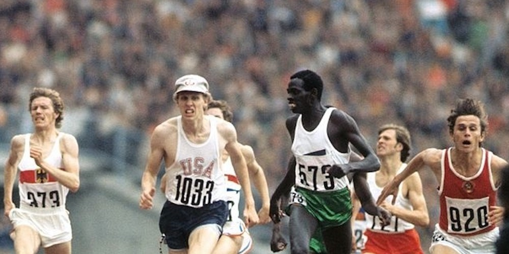Runners on an athletics track. A man in a white cap is narrowly in the lead.