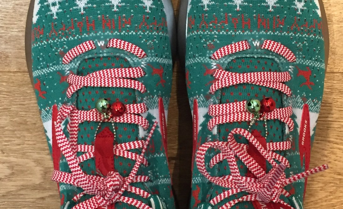 Pair of knitted trainers with in green with red and white patterns and red and white laces with bells on them.