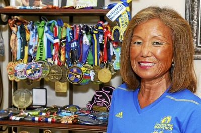 Mature Korean woman standing next to a rack of medals.