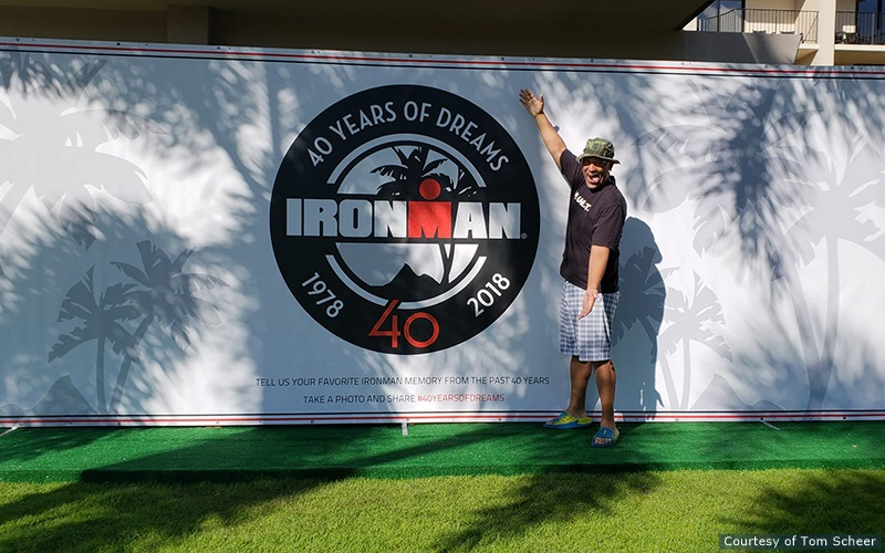 Man Standing next to a sign about the 40th anniversary of Ironman.