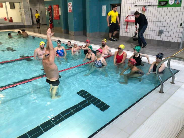 Swimmers long the edge of a pool with Duncan Goodhew demonstrating arm position.
