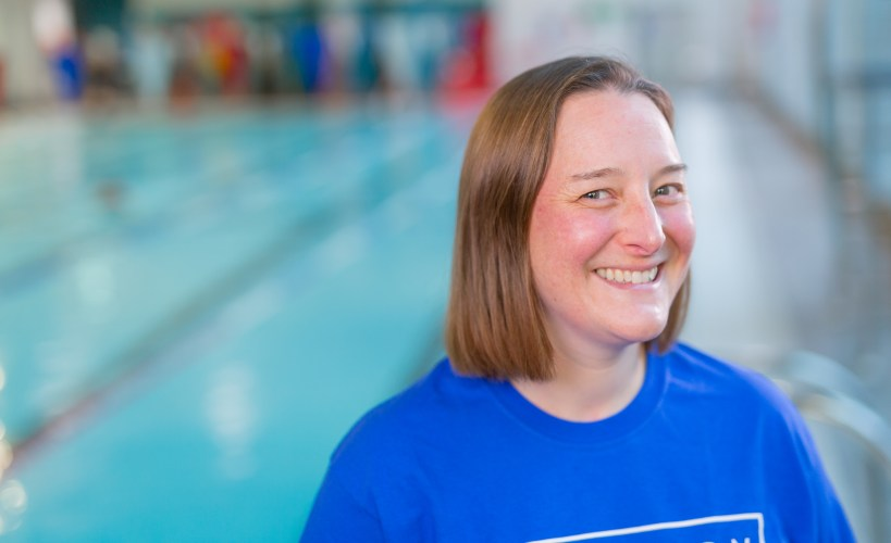 Tamsyn standing next to a swimming pool whilst wearing a Swimathon t-shirt