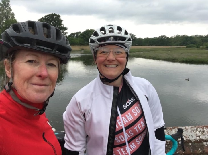 Teri and Tamsyn wearing cycling kit, posing by a river.