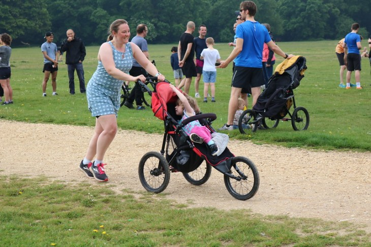 Tamsyn running whilst pushing a buggy. She is wearing a Ruu-Muu running dress made by Nuu-Muu.