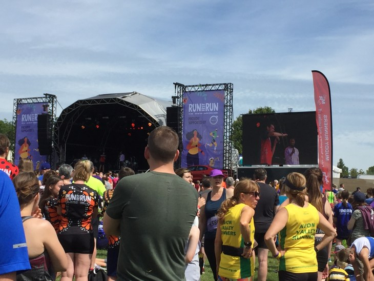 A crowd of runners at RunfestRun a new UK running festival. The runners are watching a stage where Colin Jackson is talking to Vassos Alexander.