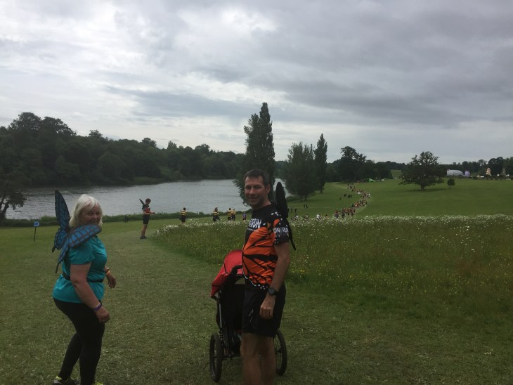 Stuart and Sandra with the buggy near the end of the Big Bug Run. A trail of runners can be seen off into the distance. They are at the top of a hill overlooking a lake.
