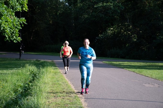 A woman wearing vibrant leggings running towards the camera and smiling showing that she's feeling positive.