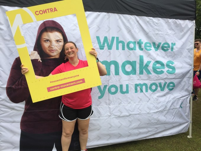 Tamsyn wearing a Contra t-shirt in front of a Contra poster.