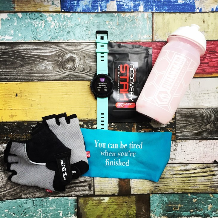 Flaylay of cycling mitts, a headband with the slogan 'You can be tired when you're finished', a Garmin showing the training status 'peaking', a sachet of recoverystak and a Fullsteam bottle.