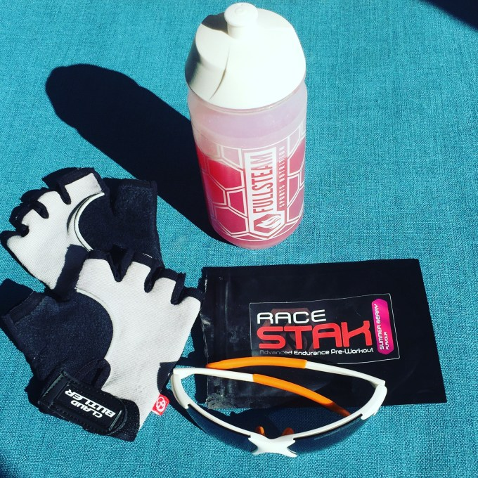 Flatlay of cycling mitts, sunglasses, a packet of Racestak pre-workout in summer berry flavour and a Fullsteam bottle.