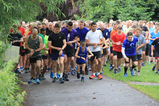 A group of people at the start of Salisbury parkrun. Most of them are glancing down at their watches.