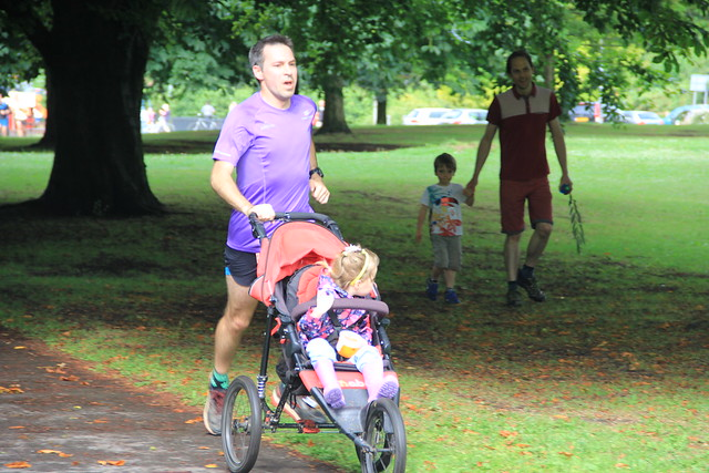 Stuart running towards the finish with M in her buggy.