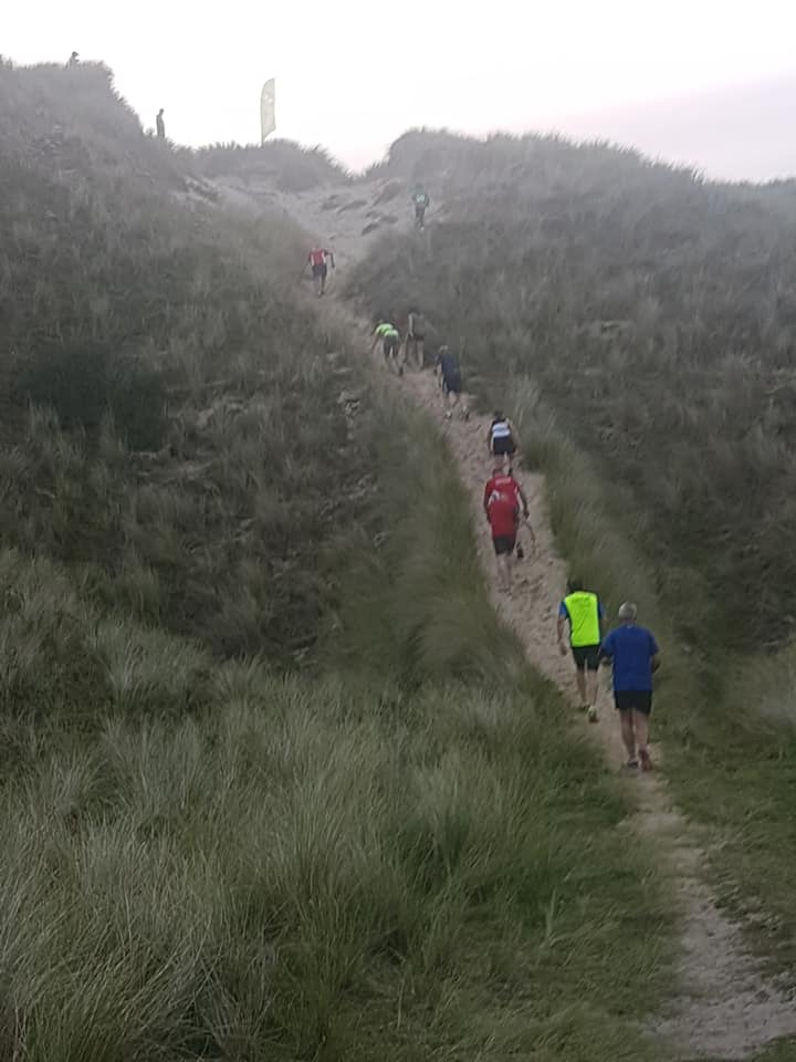 Runners tackling a large sand dune. People can be seen walking purposefully.