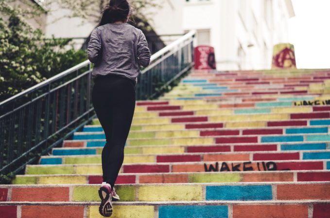 A woman running up some brightly coloured stairs.