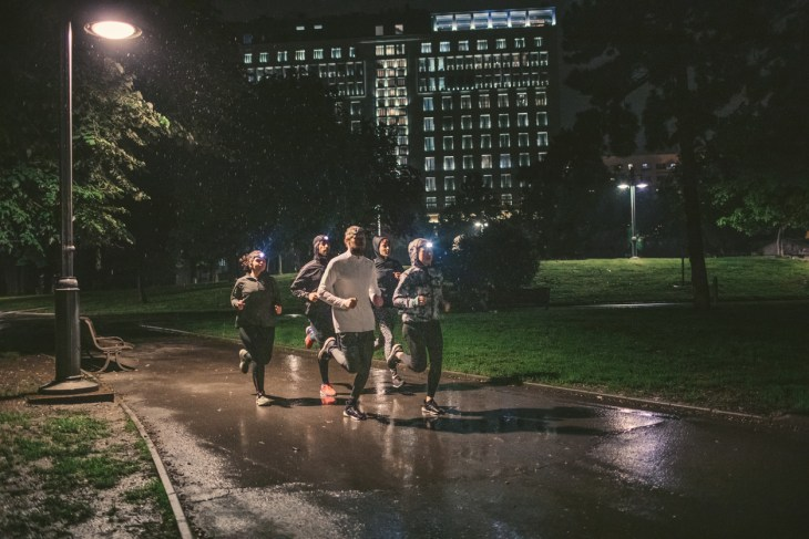 Friends training in the city park in bad weather conditions.