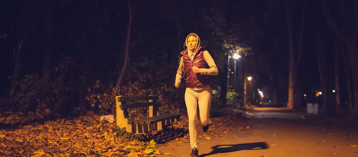 Sporty young woman, night jogging in the park under the street lights