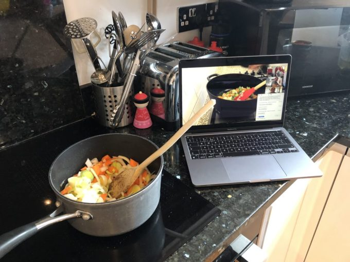 Tamsyn's kitchen. A laptop showing Kinu Yukawa's pan with vegetables and a spoon in it. This is next to Tamsyn's hob with a pan with vegetables in it.