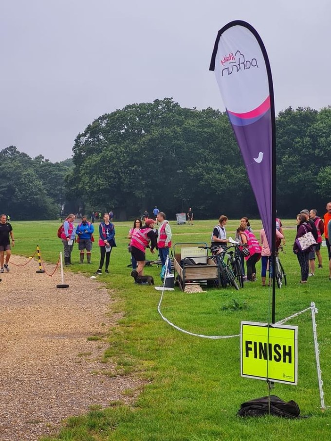 Volunteers gathering near the finish line of Southampton parkrun. There are a flag and finish sign in the foreground.