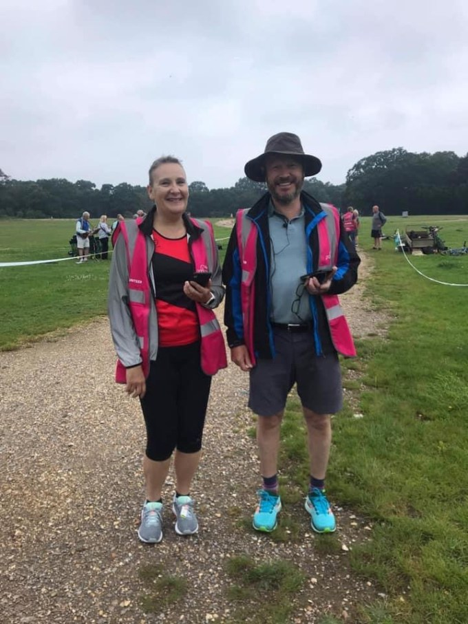 The timers standing ready near the finish of Southampton parkrun. They have pink high vis vests on and are holding mobile phones.