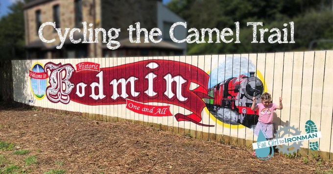 Sign painted on a fence that says Bodmin with a steam train next to it.