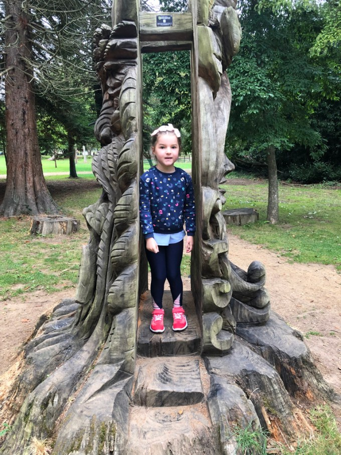 A young girl standing in the hollow centre of a carved tree.