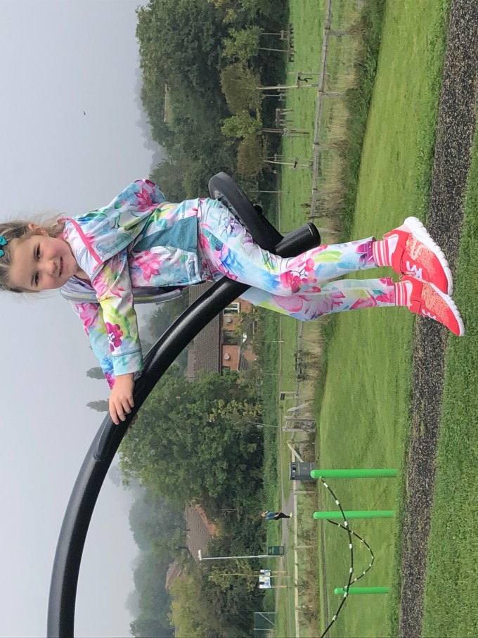 M sitting on a seesaw.