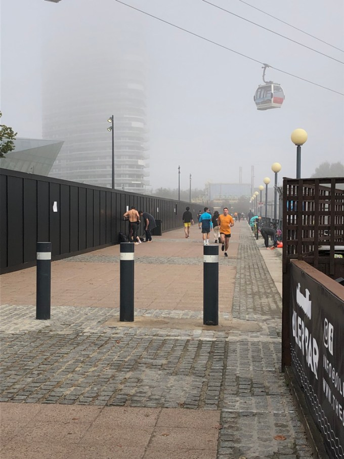 Stuart running in the final 100m of Victoria Dock parkrun. Swimmers can be seen near him and there is a cable car visible in the mist.