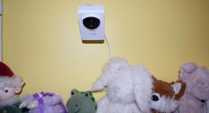 A Cocoon Cam mounted on a yellow wall above a crib with stuffed animals on the railing