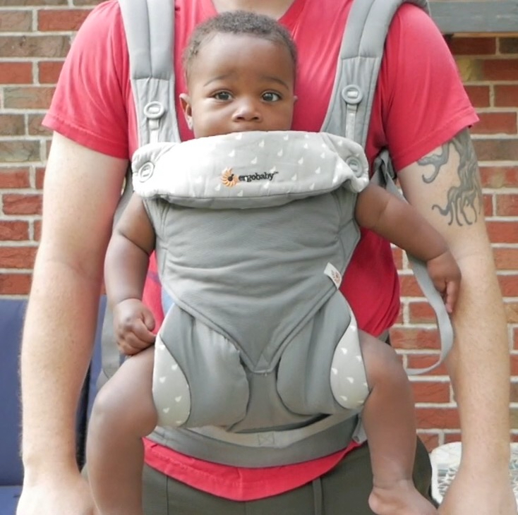A baby in the Ergobaby 360 carrier being carried by a guy with a red shirt