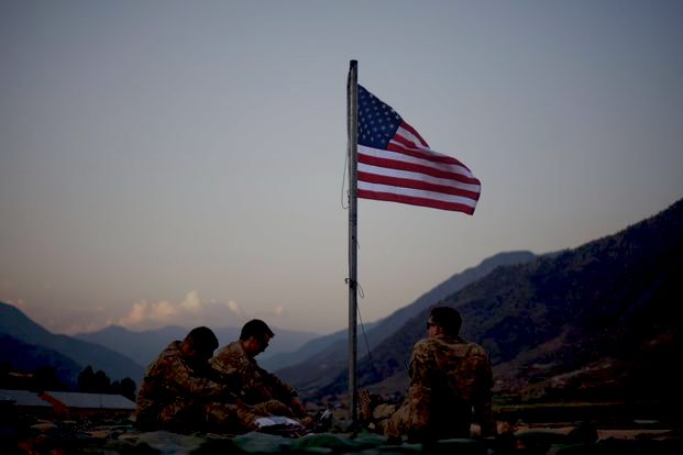 Soldiers beneath an American flag in Afghanistan.