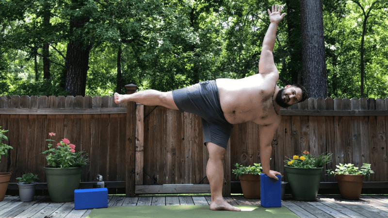 Marc practicing Half Moon in the Garden using a Yoga Block for Support