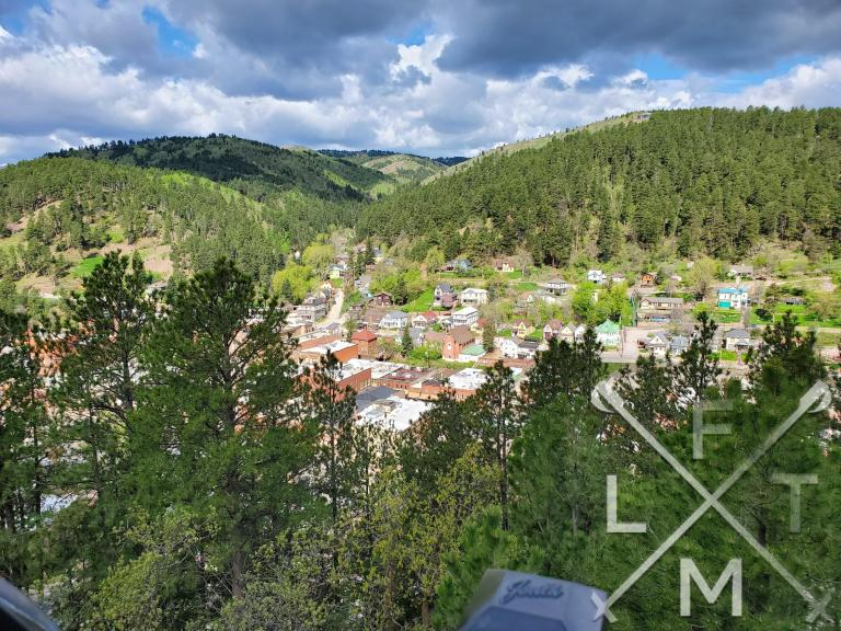 a wide view looking down onto the town of Deadwood.  In the immediate foreground are the tops of green trees.  In the middle is the town itself and in the background are rolling hills covered with evergreen trees.