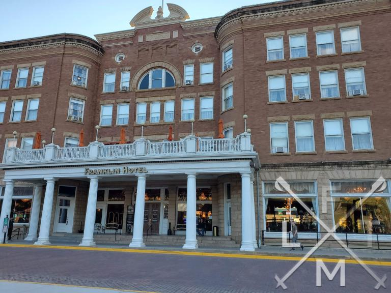 A view of the front of the Franklin hotel.  The building is brick made with white stone columns in the front.