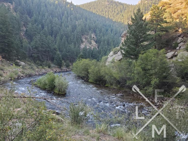Clear Creek bending in a crescent moon arch surrounded by hills filled with evergreen trees
