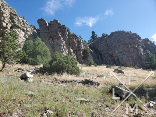 The Scorch of the Hiking Seasons as depicted by the sun hitting some rock formations with dried grass all around.