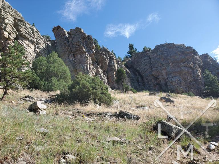 A wall of rock that towers above the trail.