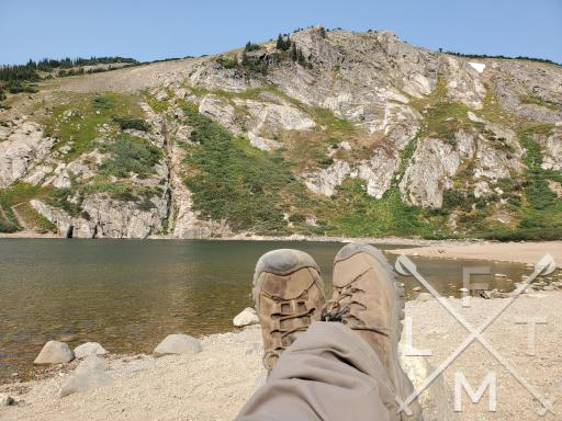 My Keen's at St. Mary's Glacier kicked up relaxing on a rock by a lake with a mountain in the background.