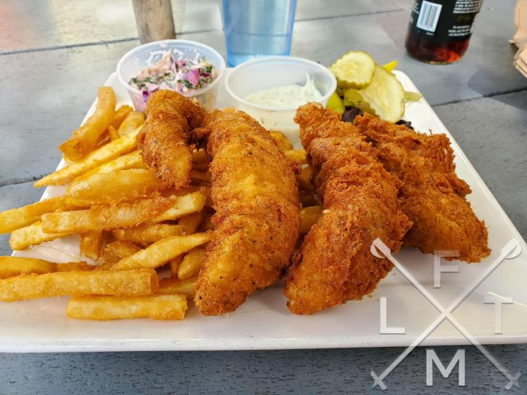 Three big fried fish filets and fries with tarter sauce, cole slaw, and a small salad of pickles and peppers.