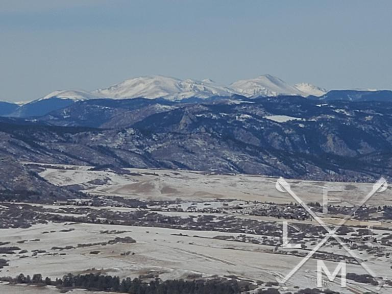 Snow covered mountain tower over the foothills as seen from the Ridgeline Open Space Loop hike.