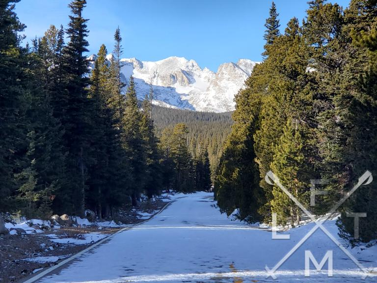 The walk up the entry road towards Brainard Lake.  Snow covers the road with pine trees with deep green needles on either side of the road.  At the end of the road are the snow covered Indian Peaks range on the way to the Long Lake Loop in winter.