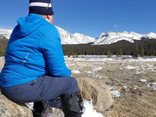Me sitting on a rock looking at snow capped mountains.  One of the stages I have found in the mental health benefits of hiking is wonder and I am looking in awe at some snow covered peaks.