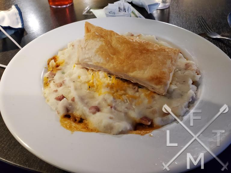 The big plate of Shepherd's Pie from Lonigans Irish Pub.  A puff pastry sits on top of a mound of mash potato's covered in cheese.  A bit of marinara sauce can be seen on the edges.