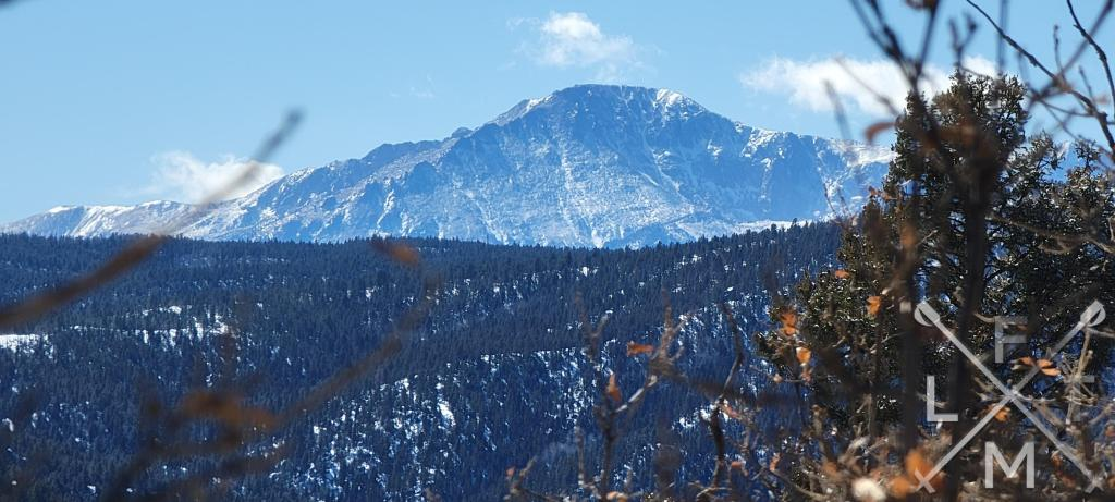 Pikes Peak towering above the trees as you descend from Chautauqua Mountain.