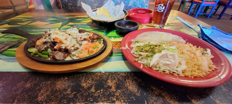 The Fajitas Texanas from Tequila's in Trinidad with smothered carne asada on one plate and rice beans and guacamole on the other plate. The meat plate is still sizzling and steaming.